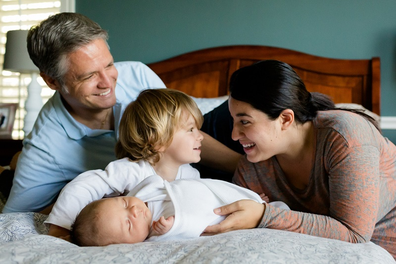 Mom Dad and kids smiling - summer could increase radon gas concerns for homeowners