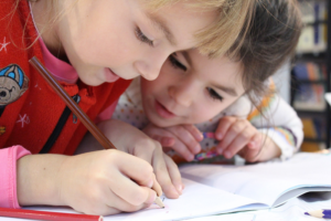 Children at a table working in a schoolbook - Schools and other buildings where people spend a lot of time should have radon inspection to ensure safety