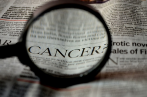 magnifying glass look at article about cancer in newspaper - radon and blood cancer link discussed by radon-rid