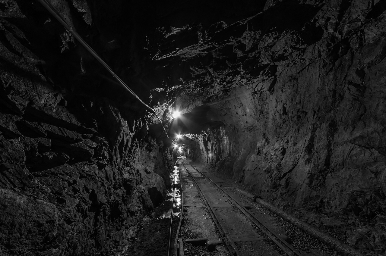 Mine shafts are important to the history of radon gas - image of black mine shaft with lights