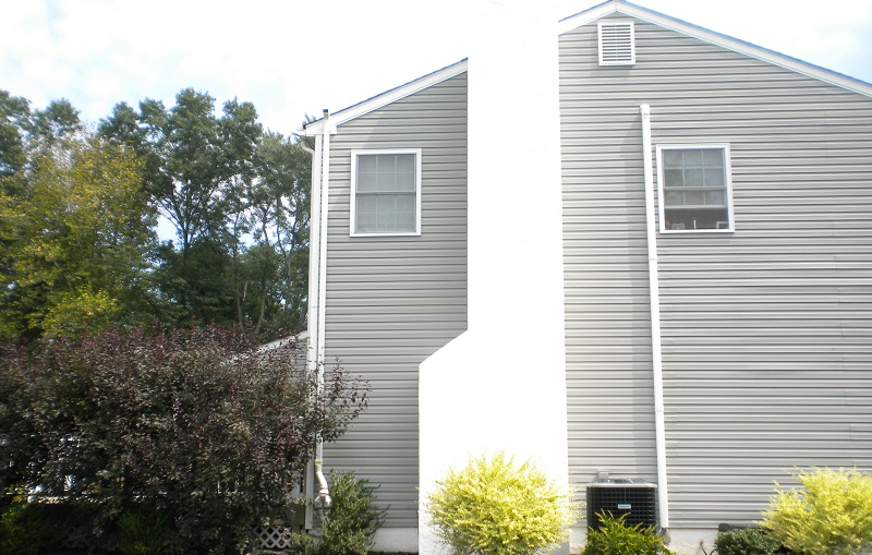 Photo of house with external radon mitigation system | FAQS about Radon Remediation | Radon-Rid, LLC.